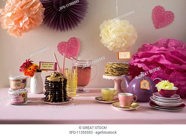 A jolly buffet decorated with paper flowers and various sweet dishes