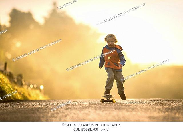 Young boy skateboarding at sunrise, Lahinch, Clare, Ireland