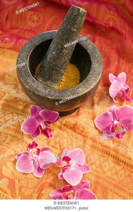 Mortar with pestle and flowers, elevated view, close-up