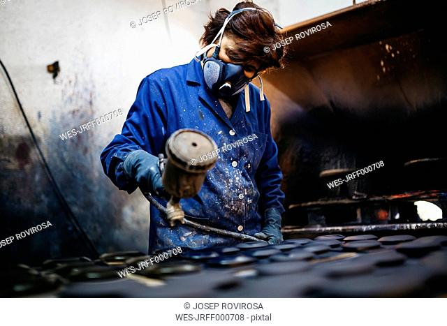 Female worker painting ceramics with spray gun