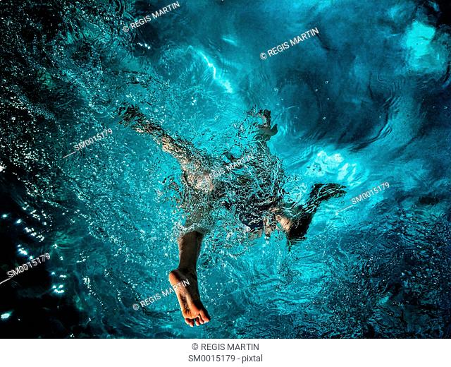 Young girl jumping in a swimming pool view from underwater