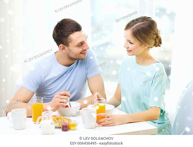 food, home, people and happiness concept - smiling couple having breakfast at home