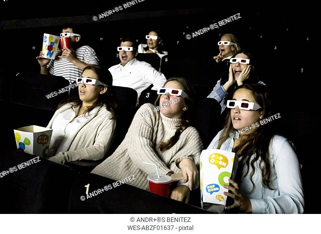 Scared people with 3d glasses watching a movie in a cinema