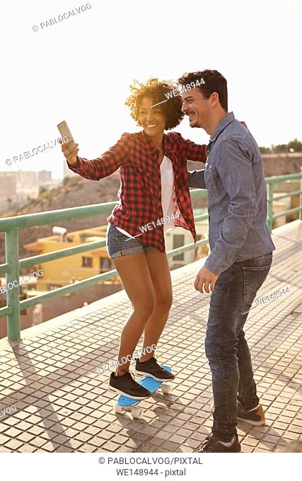 Curly haired girl posing on a skateboard while boy holds her to take a selfie of them with big toothy smiles