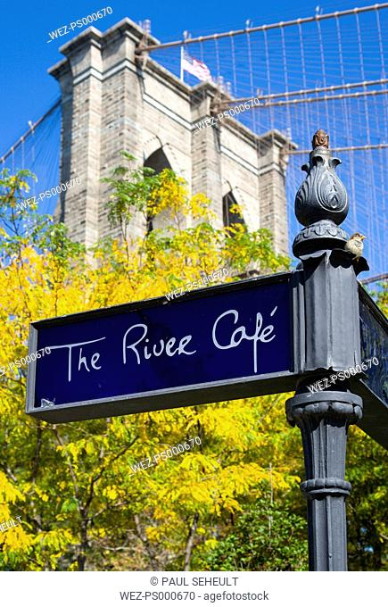 USA, New York, Brooklyn Bridge Park, signpost for The River cafe and detail of one of the suspension bridge towers