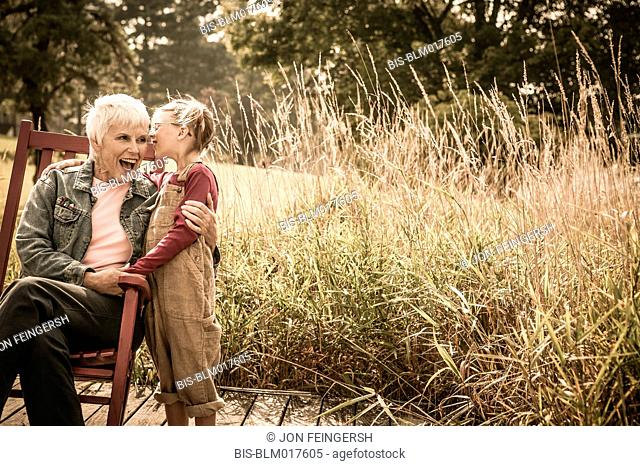 Caucasian girl whispering to grandmother outdoors
