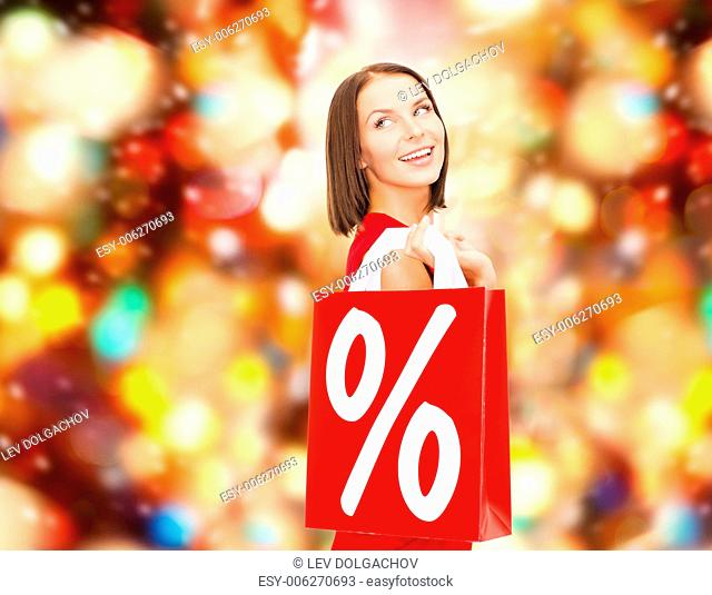 sale, gifts, christmas, holidays and people concept - smiling woman in red dress with shopping bags and percent sign over red lights background