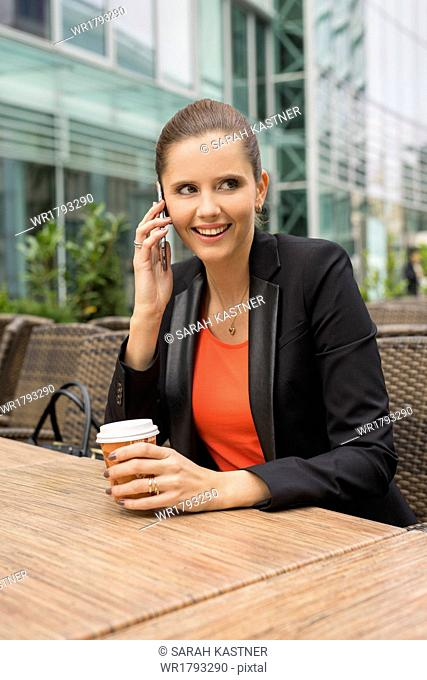 Young business woman with cellphone sitting in a cafe