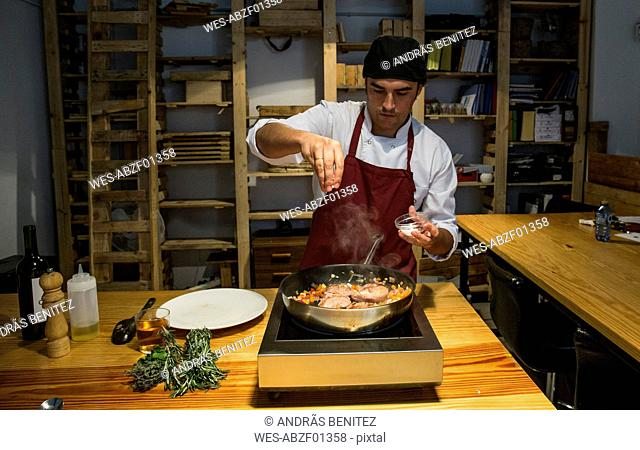 Man pouring salt on beef cheeks in a pan with sauteed vegetables