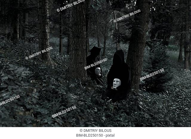 People wearing black robes and holding white masks sitting in forest