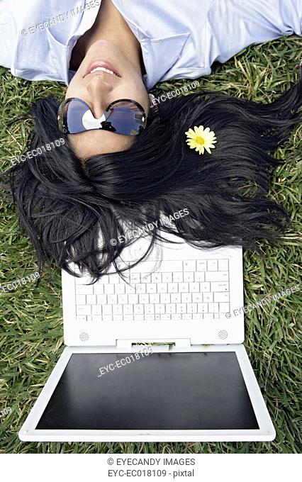View of a woman sleeping on the grass with a flower in her hair