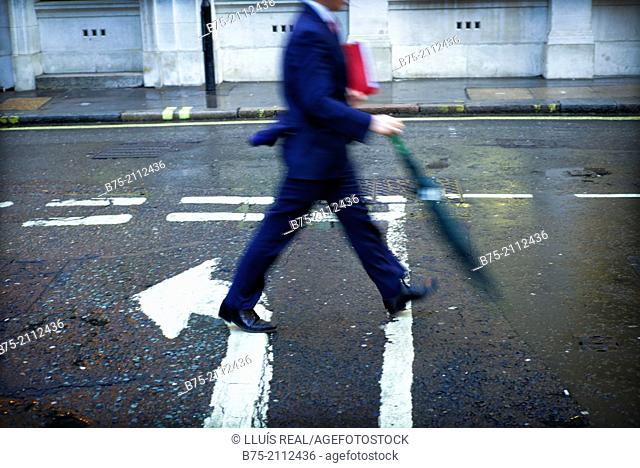unrecognizable executive man, with a folder under his arm and an umbrella walking down the street in the opposite direction of an arrow painted on the asphalt
