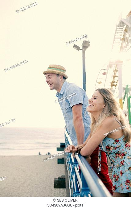 Young couple leaning on railing on Santa Monica pier, California, USA