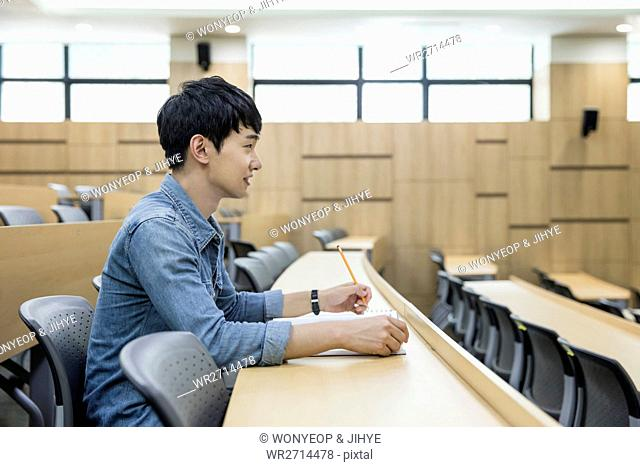 Side view of male college student in lecture room