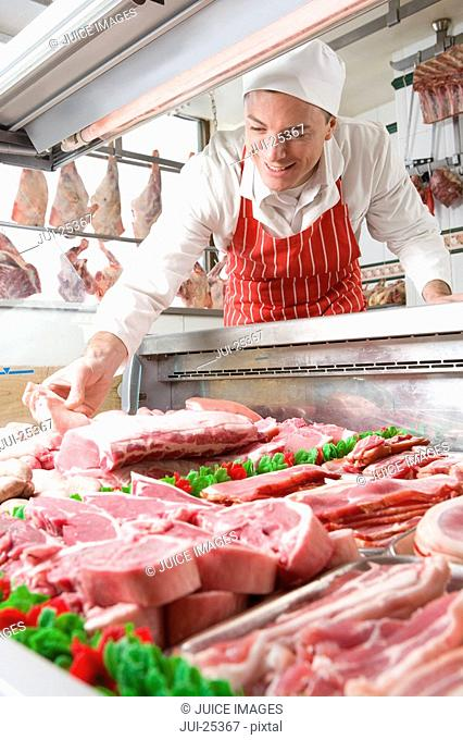 Smiling butcher arranging meat in display case