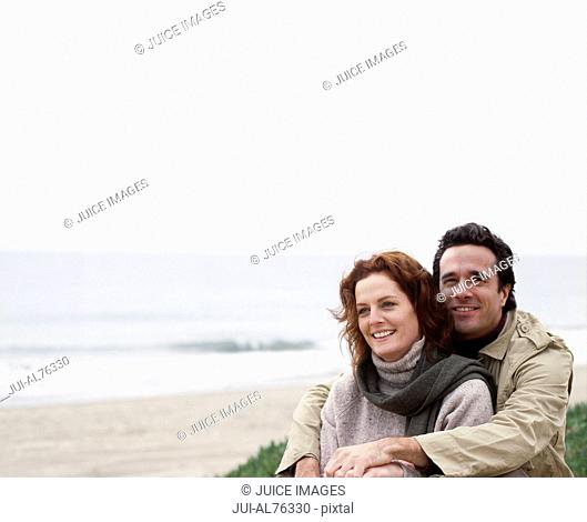 Portrait of a young couple embracing on the beach