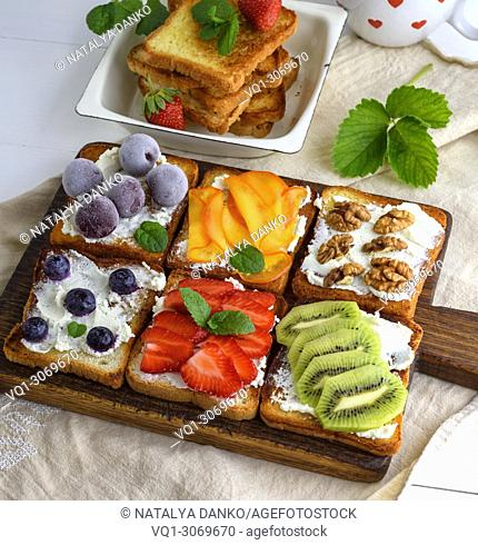French toasts with soft cheese, strawberries, kiwi, walnuts, cherries and blueberries on a brown wooden board, top view