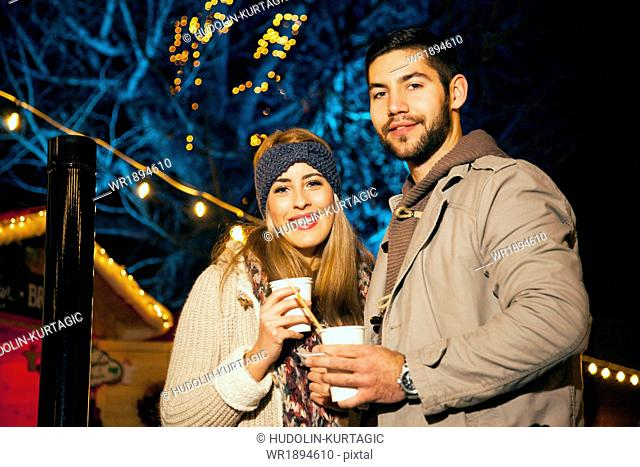 Young couple drinks punch at Christmas Market