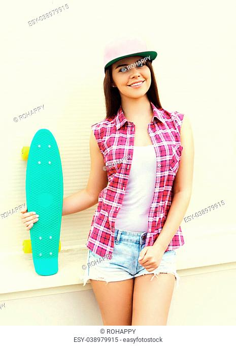 Fashion hipster cool girl in colorful pink clothes with skateboard having fun over white wall