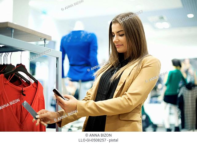 Attractive woman checking bar code in shopping mall Debica, Poland