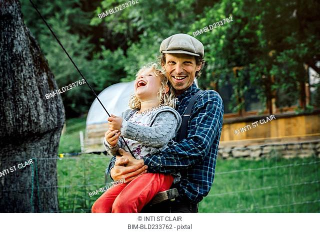 Caucasian man hugging daughter on rope swing