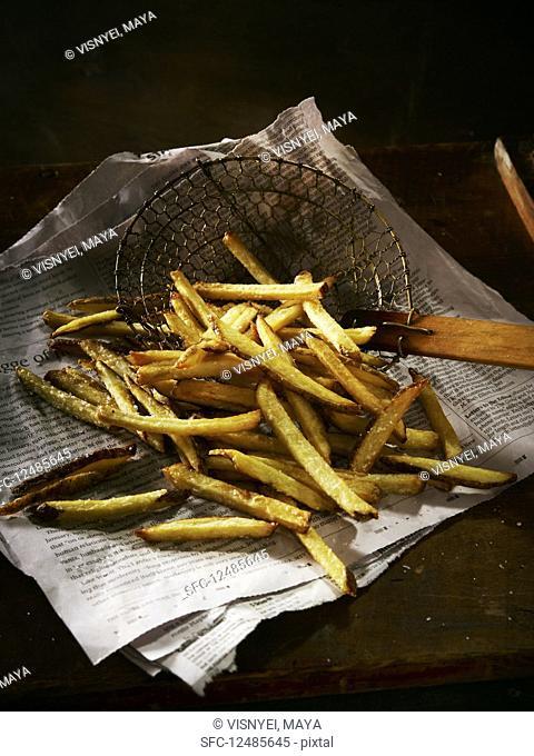 Fresh fries in a basket on newspaper