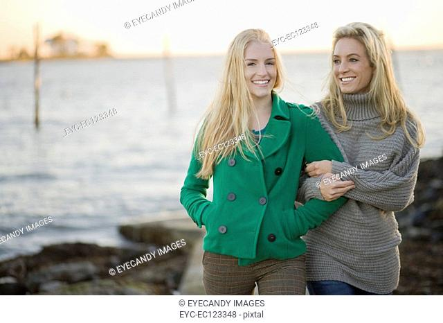 Portrait of young happy women arm in arm near the ocean on coast