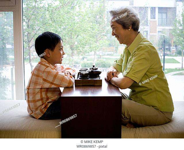 Grandmother and grandson sitting cross legged drinking tea