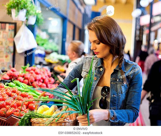 Beautiful young brunette woman on a market getting fresh food