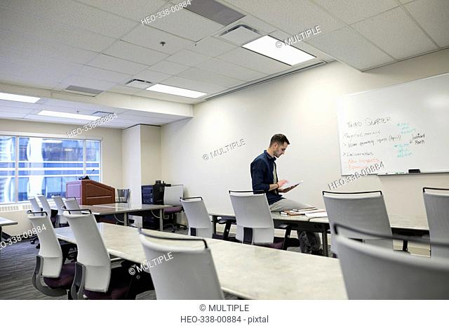 Businessman preparing at whiteboard in empty office classroom