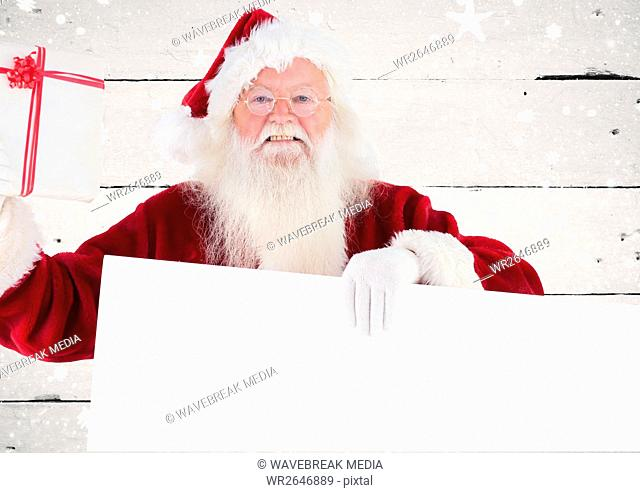 Happy santa claus holding blank placard and gift box