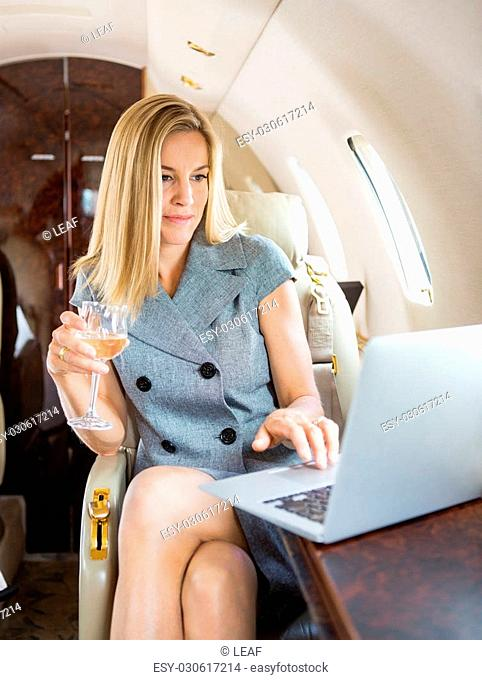 Beautiful businesswoman holding wineglass while using laptop in private jet
