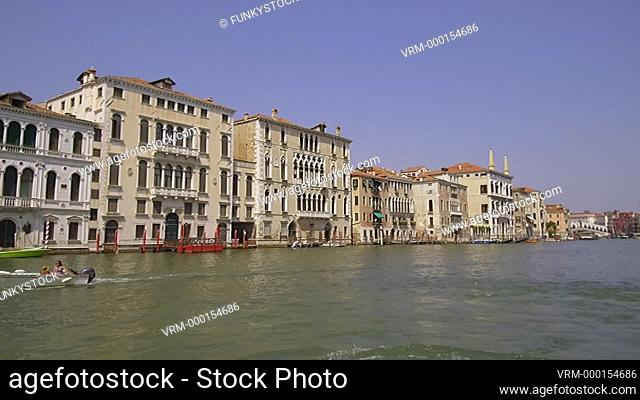 Tracking moving shot along the central Grand Canal passing a Gondola below the Rialto showing Venetian Palaces, Venice, Italy