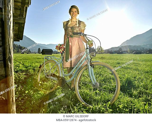 Woman by bicycle, mountain pasture