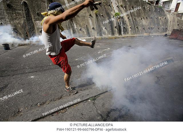 21 January 2019, Venezuela, Caracas: A masked demonstrator jumps when security forces throw tear gas at him in a collision