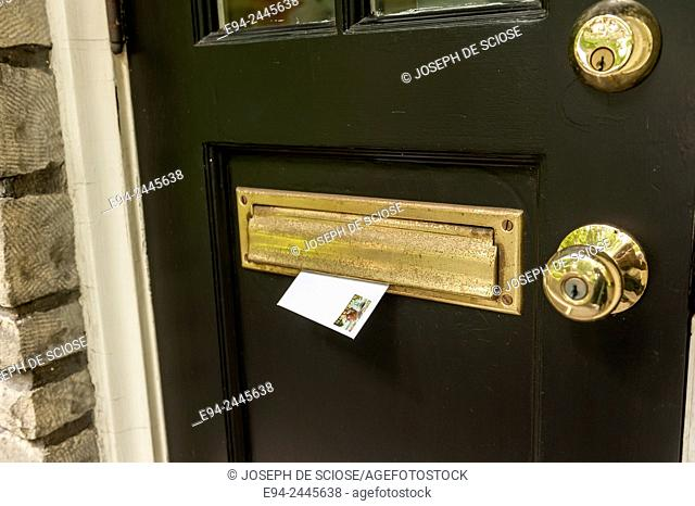 A stamped envelope in a mail slot on a door for the mailman to pickup. Pittsburgh Pennsylvania USA