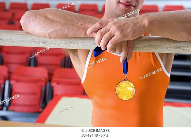Male gymnast with gold medal, arms on bar, mid section