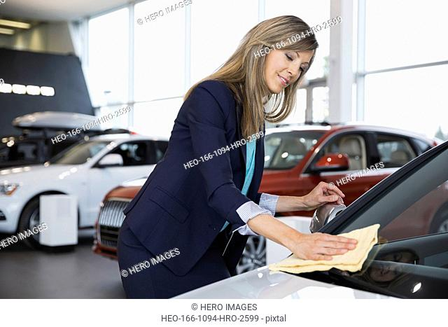 Saleswoman wiping windshield in car dealership showroom