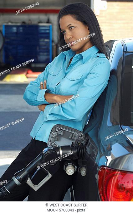 Woman leaning on car with gas pump in it