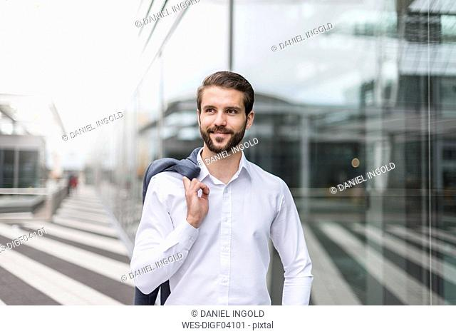 Portrait of smiling young businessman at glass facade