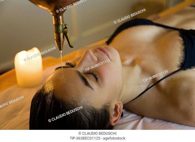 Woman getting ayurvedic oil treatment shirodara