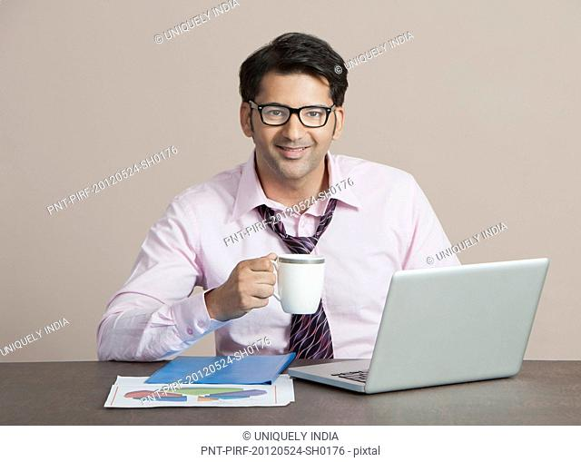 Businessman sitting in front a laptop having coffee
