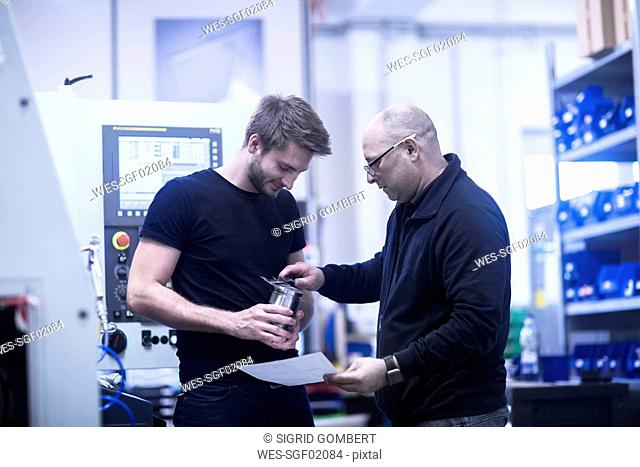 Two men at work in a factory