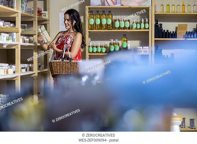 Woman taking product from shelf in health shop