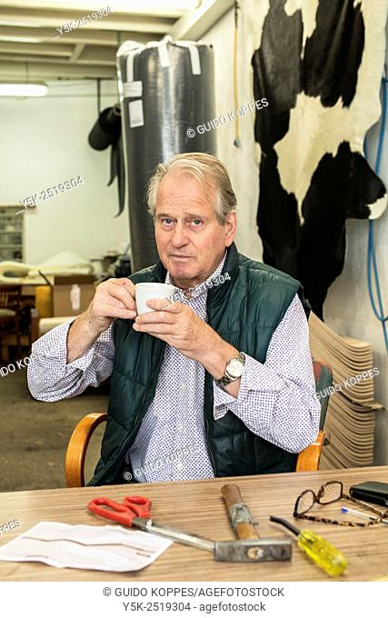 Tilburg, Netherlands. The 72 year old upholsterer Boy drinking a cup of coffee at his workbench, while suffering from artritis in his hands