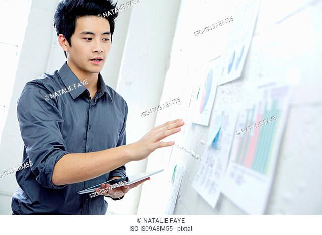 Young man in office explaining wall presentation