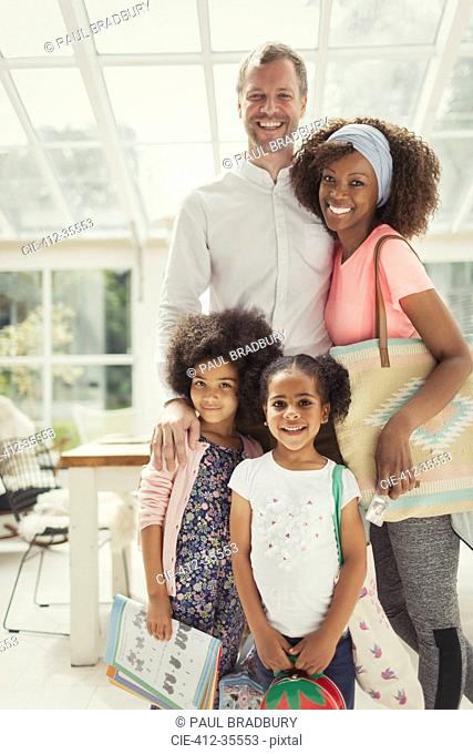 Portrait smiling multi-ethnic young family ready to leave the house