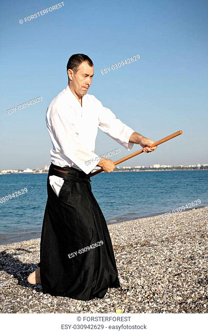 Guy in kimono with stick exercising aikido on beach in morning