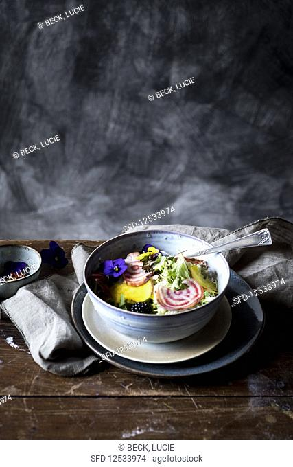A bowl with salad and eatable flowers at a wooden table from the side
