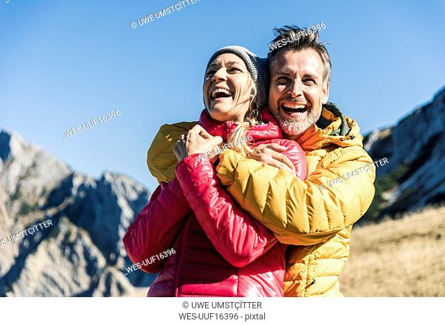 Austria, Tyrol, happy couple hugging on a hiking trip in the mountains